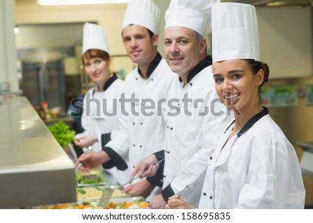 Four chefs smiling at camera while working at serving trays in busy kitchen