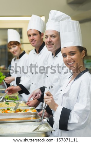 Four chefs working at serving trays smiling at camera in busy kitchen
