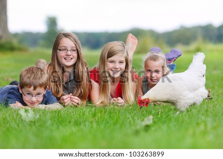 four children on a meadow with a white chicken - stock photo