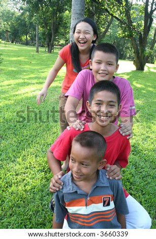 Four children playing in the park. - stock photo