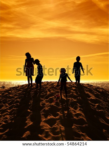 four children playing on a sand hill at the beach in sunset, high contrast