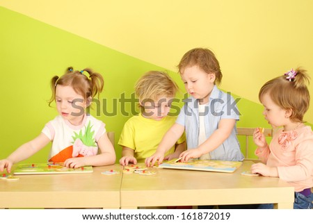 Four children playing with wooden toys, sitting at the table