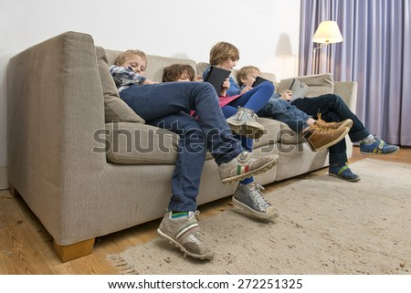 Four children, slouching on a couch in a living room, gaming on tablets and smart phones, being bored - stock photo