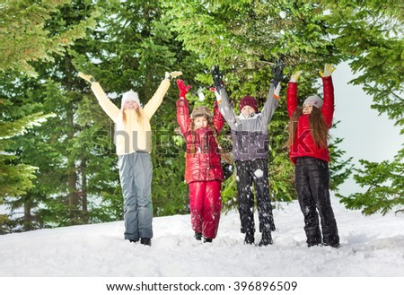 Four children standing in row at the winter forest - stock photo