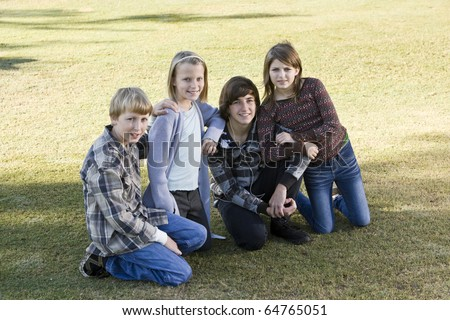 Four children (10 to 15 years) posing together on grass
