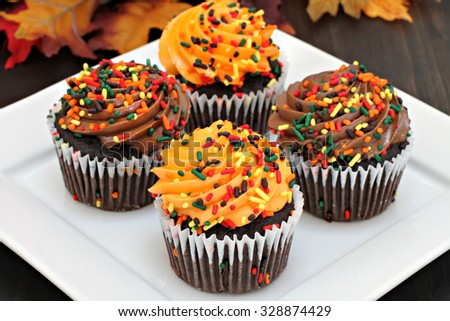 Four chocolate cupcakes frosted in chocolate and orange with sprinkles for autumn.  Selective focus on front cupcake. - stock photo