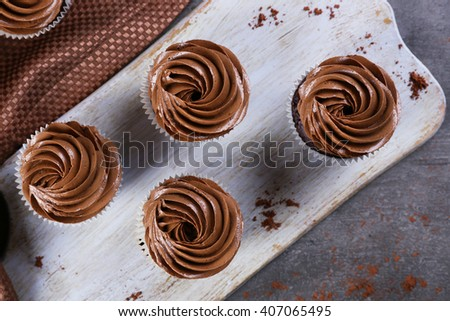 Four chocolate cupcakes on a tray over grey background, close up - stock photo