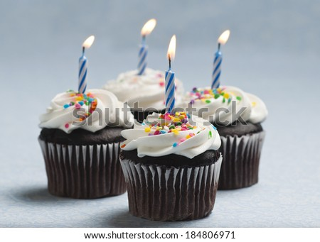 Four chocolate cupcakes with frosting, sprinkles and burning candles. - stock photo