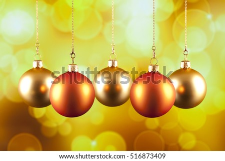 Four Christmas baubles on yellow background
