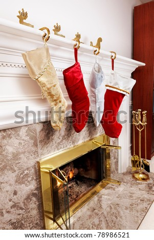 Four Christmas stockings hanging at the fireplace - stock photo