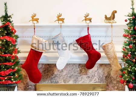 Four Christmas stockings hanging on the mantelpiece