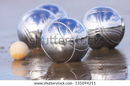 Four chrome boules and a cochonnet on a wet sandy beach. - stock photo