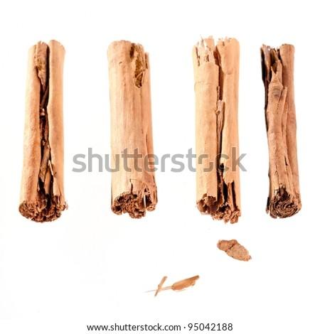 four cinnamon sticks isolated on white. High angled cinnamon sticks on white background. - stock photo