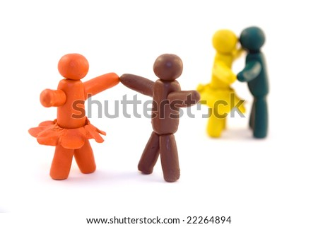 Four clay human figures dancing isolated on white background - stock photo