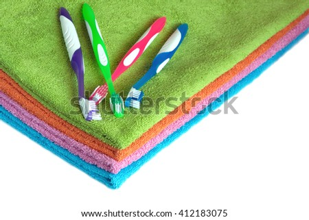 Four clean soft double bath towels set of different colors stacked and four toothbrushes isolated on white background. Side view from corner close-up - stock photo