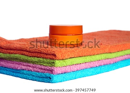Four clean soft double bath towels set of different colors stacked and jar of cosmetic skin cream isolated on white background. Side view from corner close-up - stock photo