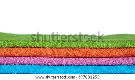 Four clean soft double folded bath towels set of different colors stacked isolated on white background. Horizontal front view close-up - stock photo