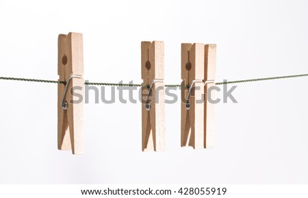 Four clothespins hanging on the clothesline isolated on white background - stock photo