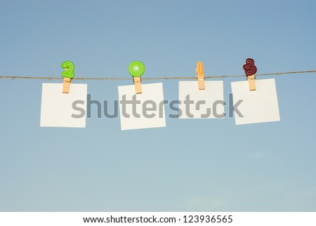 Four clothespins on rope, 2013. - stock photo