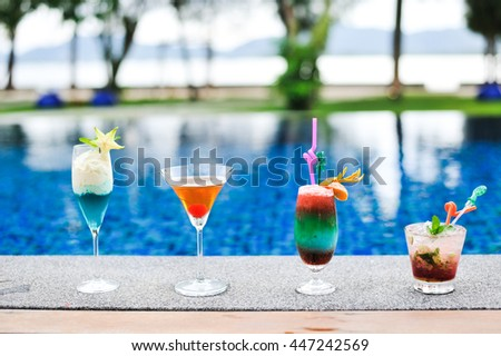 Four cocktail glasses beside swimming pool.