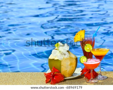 four cocktails near the swimming pool - stock photo