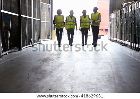 Four colleagues in reflective vests walking into a warehouse - stock photo