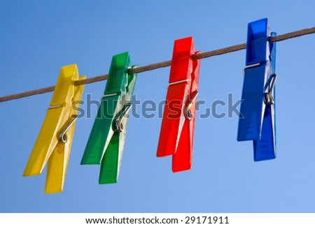 four color clips on rope  against blue sky - stock photo