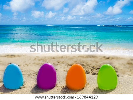 Four color Easter eggs on the sandy beach by the ocean - stock photo