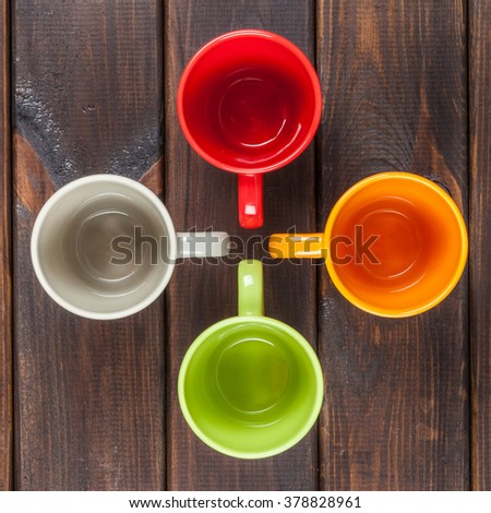 Four color tea cups arranged in a cross, top view - stock photo