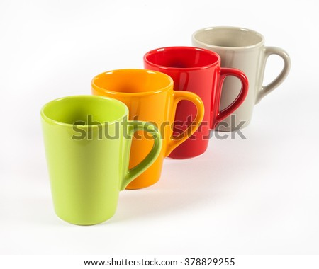 Four color tea cups shown in row - stock photo