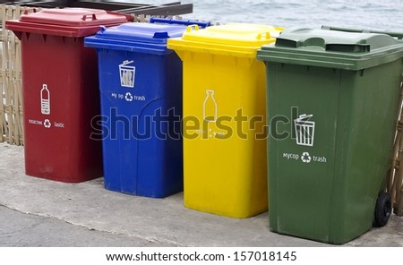 Four color trash cans in the park beside the walk way. - stock photo