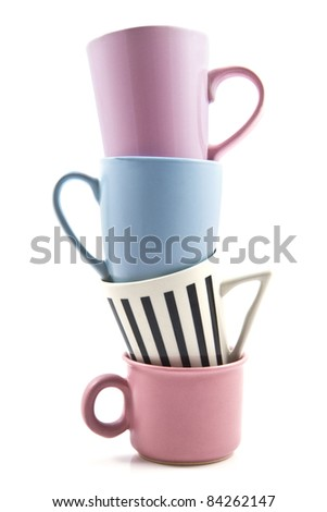 Four colored cups on a pile over white - stock photo