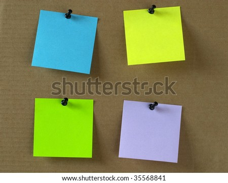 Four colored empty sticker notes on a cardboard with push-pins - stock photo