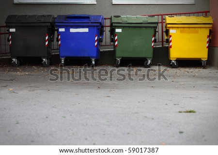 Four colored garbage bins to help separate and recycle - stock photo