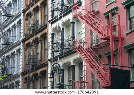Four colorful, blue, brown, white and red apartment buildings facades with emergency escapes. Typical New York City rental complexes with fire escape stairs next to the windows. - stock photo