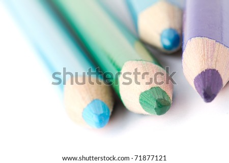 Four colorful crayons on white background with a shallow depth of field for effect. - stock photo