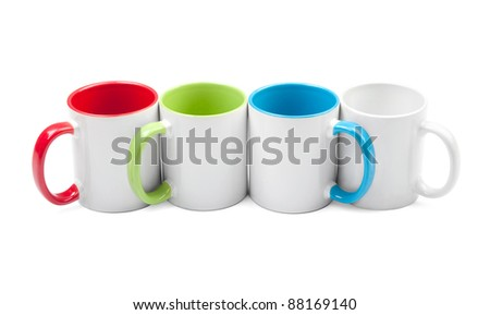 four colorful cups in a row on a white background - stock photo
