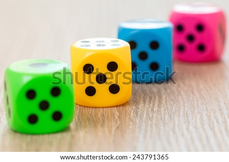 Four colorful dice on the wooden surface. Selective focus. - stock photo