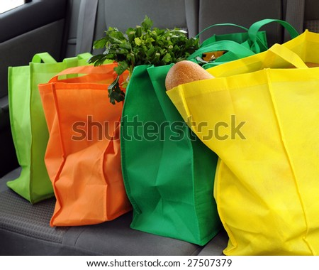 Four colorful eco-friendly shopping bags filled mostly with groceries in the back seat of a car. - stock photo