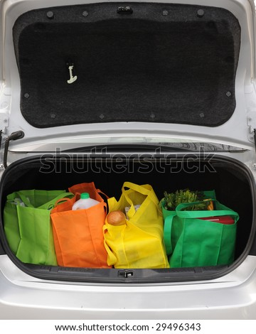 Four colorful eco-friendly shopping bags filled mostly with groceries in the opened trunk of a car.  Open trunk provides negative space for your message.