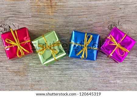 Four colorful gift boxes on the wooden floor - stock photo