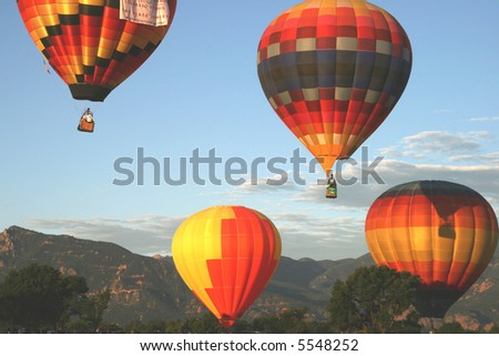 Four colorful hot air balloons during early morning ascend. Mountains in background - stock photo