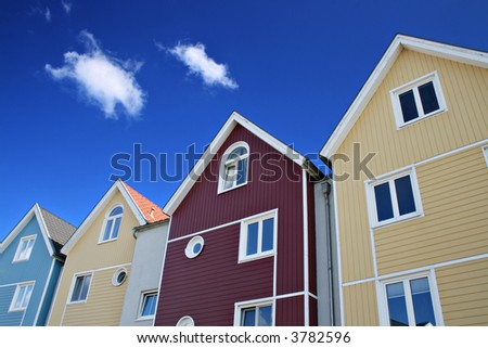 Four colorful houses with blue sky - stock photo