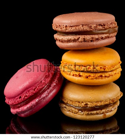 Four colorful macarons isolated on black background