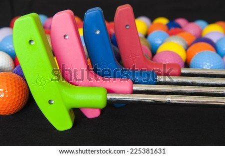 Four colorful mini golf putters with and assortment of balls - stock photo