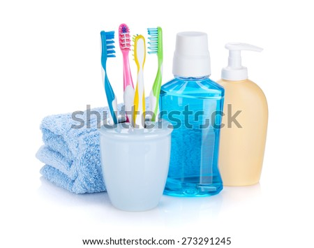 Four colorful toothbrushes, cosmetics bottles and towel. Isolated on white background - stock photo