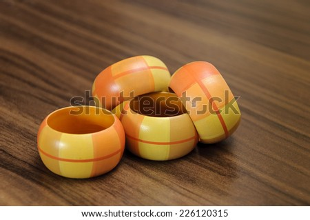 four colorful wooden bracelet on brown background - stock photo