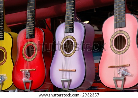 Four colourful toy guitars hang outside a small shop - stock photo
