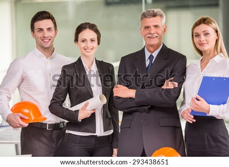 Four conficent architects standing at modern office and looking at camera. - stock photo