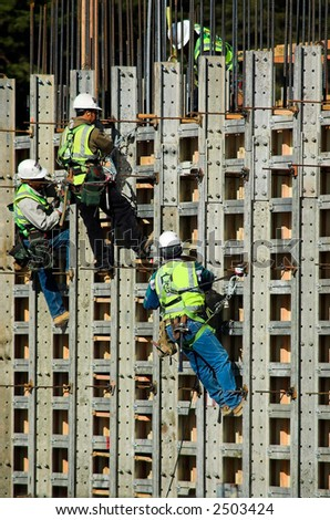 Four construction workers high up on the wall of a new building - stock photo